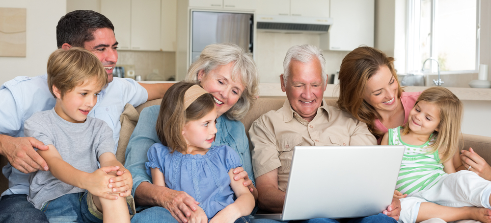 Smiling multigeneration family using laptop in living roomCROPPED
