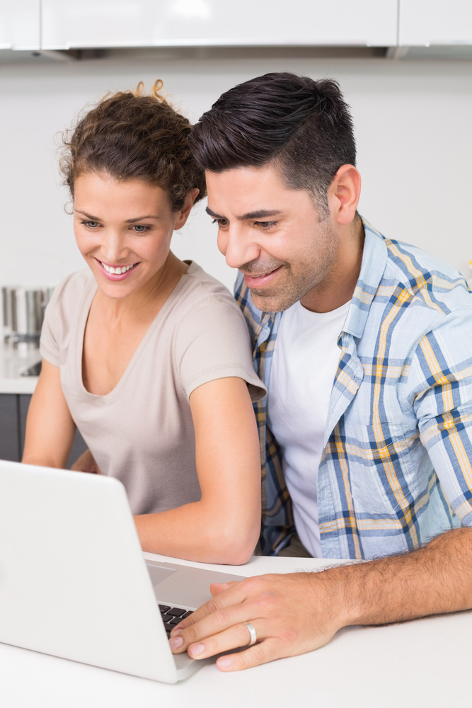 Smiling couple using laptop together at home in kitchen
